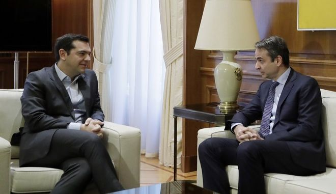 Greek Prime Minister Alexis Tsipras, left, listens to the leader of conservative main opposition New Democracy party Kyriakos Mitsotakis at Maximos Mansion in Athens on Monday, Jan. 9, 2017. Tsipras will meet the Greek political leaders on Monday to discuss the upcoming negotiations in Geneva with EU, Britain, Greece and Turkey that would reunite the divided Mediterranean island of Cyprus after more than four decades. (AP Photo/Thanassis Stavrakis)