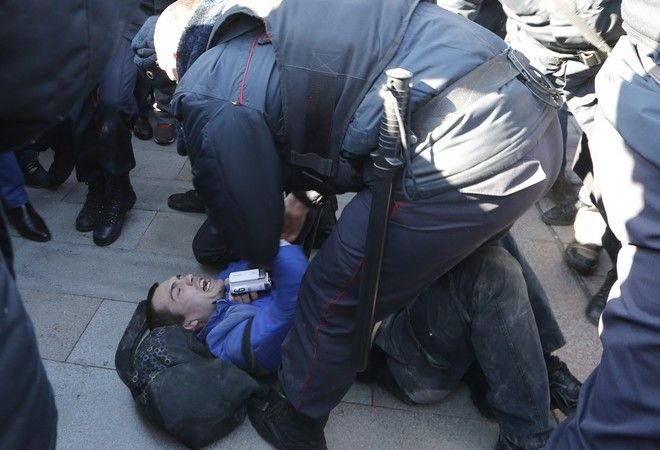 Police detain a protester in downtown Moscow, Russia, Sunday, March 26, 2017. Russia's leading opposition figure Alexei Navalny and his supporters aim to hold anti-corruption demonstrations throughout Russia. But authorities are denying permission and police have warned they won't be responsible for