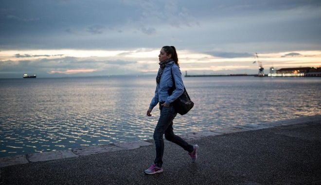A woman walks at Thessaloniki seafront promenade during the sunset in Thessaloniki on October 23, 2014. /                  23    2014.