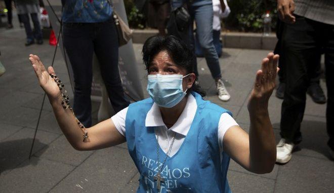 Γυναίκα με μάσκα προσεύεχεται στο Μεξικό