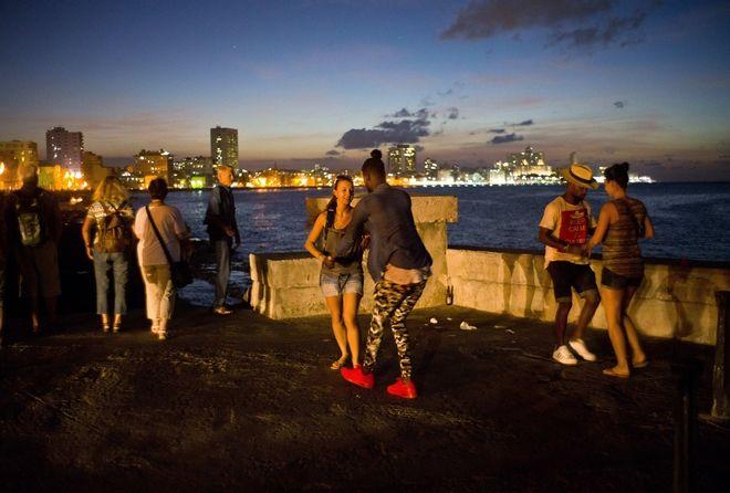Δύο Κουβανοί χορεύουν σάλσα με δύο τουρίστριες το σούρουπο στη Μαλεκόν, στην Αβάνα