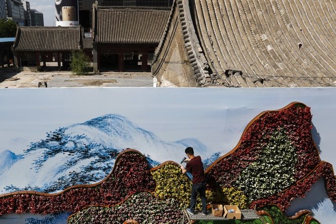 A worker installs a mountain-shaped flowers decoration on a board covering a partially demolished old courtyard houses near the Xidan Cultural Square ahead of the Belt and Road Forum for International Cooperation in Beijing, Wednesday, May 10, 2017. Leaders of 28 countries including Russian President Vladimir Putin are set to attend the Chinese summit showcasing President Xi Jinping's signature foreign policy plan, and will be held in the capital city from May 14-15. (AP Photo/Andy Wong)