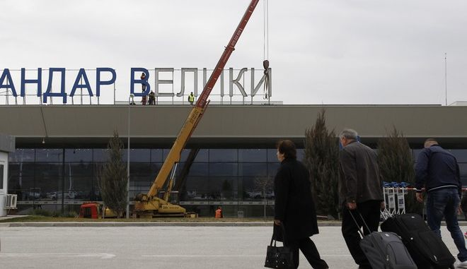 "Passengers walk towards the airport building, as workers remove giant letters from the signb reading in Macedonian ""Alexander the Great Airport"", near Macedonia's capital Skopje, Saturday, Feb. 24, 2018. Macedonian government decided recently to rename the country's main airport which carried the name of the ancient warrior king Alexander the Great, as Skopje International Airport, in a goodwill gesture toward neighboring Greece. (AP Photo/Boris Grdanoski)"