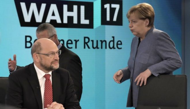 German Chancellor Angela Merkel, head of the Christian Democratic Party CDU, passes by her challenger Martin Schulz, head of the Social Democratic Party SPD, left, prior to a TV talk of the party leader in Berlin, Germany, Sunday, Sept. 24, 2017, after the German parliament elections. (AP Photo/Gero Breloer, pool)