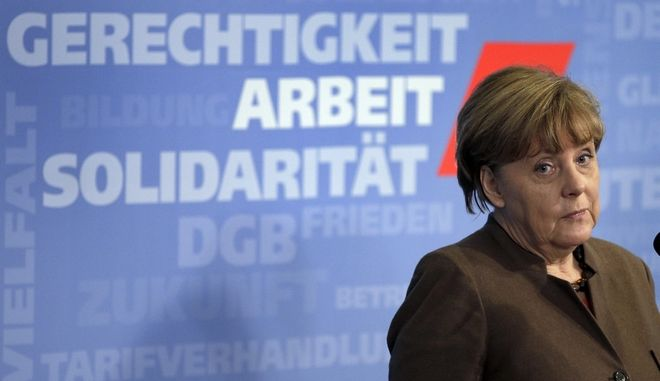 German Chancellor Angela Merkel attends a press conference after a meeting with the chairman of the German Federation of Trade Unions (DGB), Reiner Hoffmann, in Berlin, Germany, Thursday, Jan. 14, 2016. Words in the background read , from top, 'Justice, Labor, Solidarity'. (AP Photo/Michael Sohn)