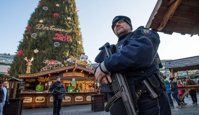 Police officers carrying  machine guns patrol at the Christmas market in Dortmund, Germany, Tuesday Dec. 20, 2016. A truck ran into a  crowded Christmas market in Berlin the evening before and killed several people. (Bernd Thissen/dpa via AP)