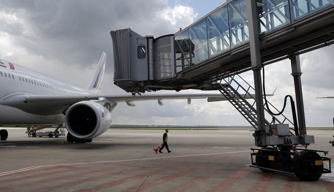 Air France ground staff works next to the Airbus A330 of the AF 738 Paris Teheran inaugural flight at Roissy Charles De Gaulle Airport, north of Paris, France, Sunday, April 17, 2016. Air France resumes flights to Iran after last year's landmark deal to curb Iranian nuclear activities, as part of larger French and European efforts to rebuild trade ties long frozen by sanctions. (AP Photo/Francois Mori)