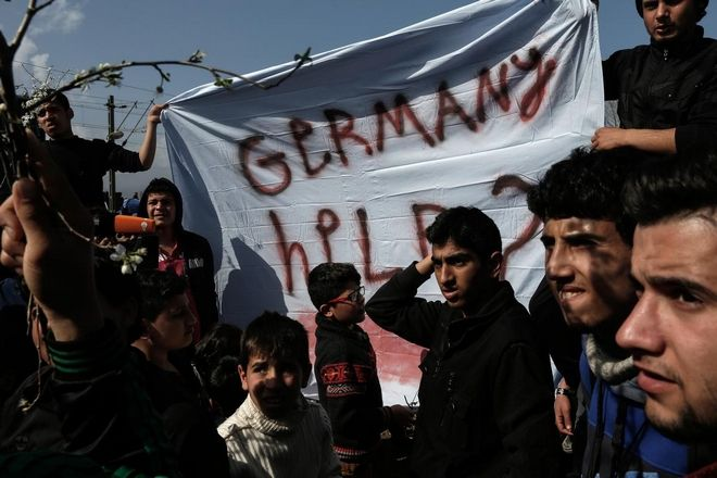 Stranded migrants from Syria and Iraq shout slogans in favor of Germany and chancellor Angela Merkel as they stage a peaceful protest calling for the opening of the border in the transit camp at the Greek-FYRO Macedonian border, near the Greek village of Idomeni, on March 1, 2016.
