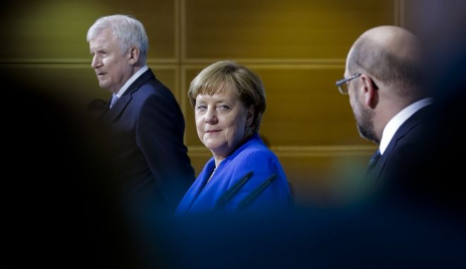 German Chancellor Angela Merkel is flanked by Bavarian governor Horst Seehofer, left, and Social Democratic Party Chairman Martin Schulz during a joint statement after the exploratory talks between Merkel's conservative bloc and the Social Democrats on forming a new German government in Berlin, Germany, Friday, Jan. 12, 2018. (AP Photo/Markus Schreiber)