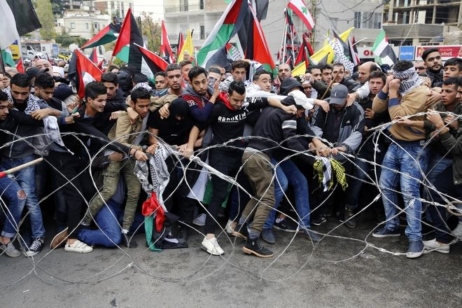 Protesters try to remove barbed wires that block a road leading to the U.S. embassy during a demonstration in Aukar, east of Beirut, Lebanon, Sunday, Dec. 10, 2017. Scores of demonstrators, including Palestinians, pelted security outside the embassy with stones and burned an effigy of U.S. President Donald Trump in a protest to reject Washington's recognition of Jerusalem as capital of Israel. (AP Photo/Bilal Hussein)