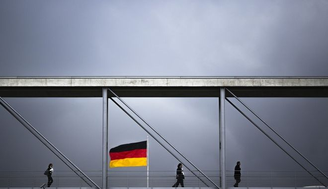 People cross a bridge between German parliament buildings on a cloudy day in Berlin, Thursday, Oct. 12, 2017. (AP Photo/Markus Schreiber)