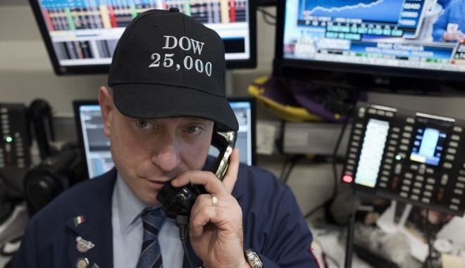 Vincent Pepe, a commodities broker with ICAP Corp., wears a Dow 25,000 hat to work at the New York Stock Exchange, Thursday, Jan. 4, 2018. The Dow Jones industrial average is trading above 25,000 points for the first time Thursday, just five weeks since its first close above 24,000. (AP Photo/Mark Lennihan)