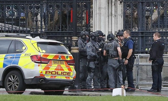 Armed police officers gather outside of the Houses of Parliament in London, Wednesday, March 23, 2017 after the House of Commons sitting was suspended as witnesses reported sounds like gunfire outside. The leader of Britain's House of Commons says a man has been shot by police at Parliament. David Liddington also said there were