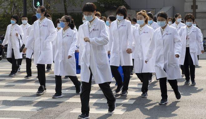Υγειονομικό προσωπικό διασχίζει δρόμο στο Πεκίνο