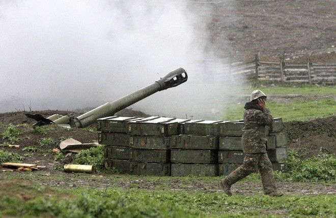 An Armenian covers his ears while a howitzer fires at an artillery position of the self-defense army of Nagorno-Karabakh near Martakert, Azerbaijan, Sunday, April 3, 2016. Azerbaijan's Defense Ministry announced a unilateral cease-fire Sunday against the separatist region of Nagorno-Karabakh, but rebel forces in the area said that they continued to come under fire from Azerbaijani forces. (Vahram Baghdasaryan, PHOTOLURE via AP)