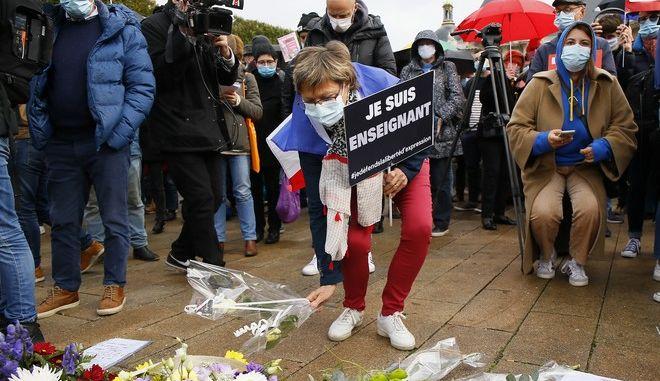 Άνθρωποι αφήνουν λουλούδια στο σημείο της επίθεσης του καθηγητή Πατί