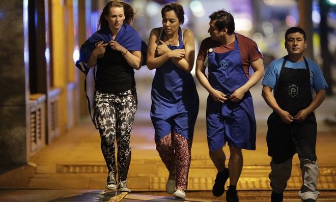 People walk away just before midnight from inside a police cordon after an attack in London, late Saturday, June 3, 2017. Armed British police rushed to London Bridge late Saturday after reports of a vehicle running down pedestrians and people being stabbed nearby. (AP Photo/Matt Dunham)