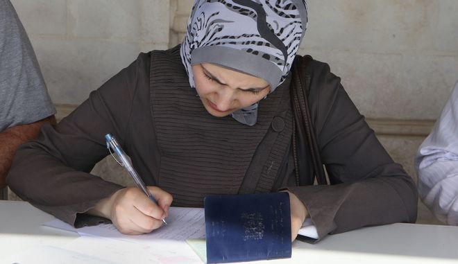 In this Tuesday, Sept. 15, 2015 photo, a Syrian fills out a form as she  prepare her documents to apply for a passport outside her embassy, in Amman, Jordan. Hundreds of Syrian refugees line up at their country's embassy every day for a long shot at a better future in Europe: They apply for Syrian passports that can get them into Turkey without visas, and from there plan to start dangerous journeys by sea and land to the continent. (AP Photo/Raad Adayleh)
