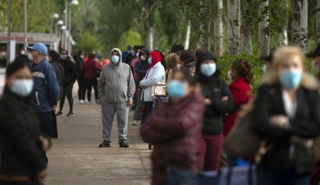 People line up as they wait to receive a ration of donated food for people at risk of social exclusion by volunteers from Aluche neighborhood association, in Madrid, Spain, Saturday, May 16, 2020.  Aluche Neighborhood association warn that the economic crisis caused by coronavirus has left many out of resources. Spain has been in lockdown to fight the coronavirus pandemic. (AP Photo/Manu Fernandez)