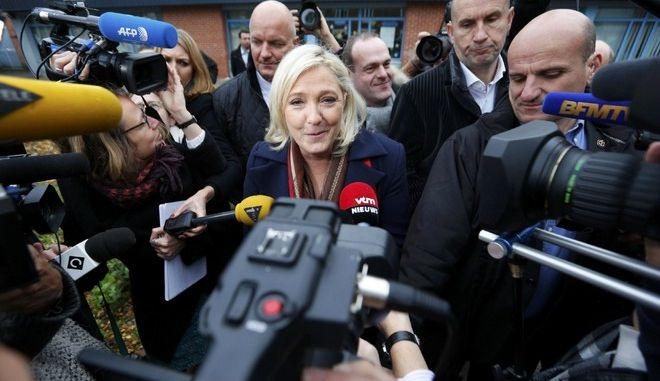 Marine Le Pen, French National Front political party leader and candidate for the National Front in the Nord-Pas-de-Calais-Picardie region, speaks to journalists as she leaves the polling station after casting her ballot in the second-round regional elections in Henin-Beaumont, France, December 13, 2015.         REUTERS/Yves Herman