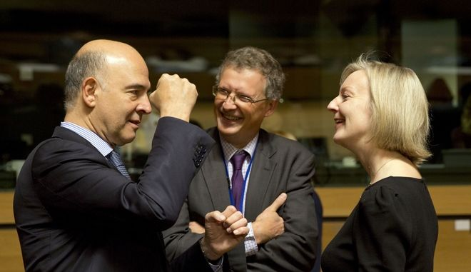 European Commissioner for Economic and Financial Affairs Pierre Moscovici, left, speaks with British Chief Secretary to the Treasury Mary Elizabeth Truss, right, during a meeting of EU finance ministers in Luxembourg, Tuesday, Oct. 10, 2017. (AP Photo/Virginia Mayo)