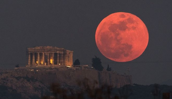 A super blue blood moon rises behind the 2,500-year-old Parthenon temple on the Acropolis of Athens, Greece, on Wednesday, Jan. 31, 2018. On Wednesday, much of the world will get to see not only a blue moon which is a supermoon, but also a lunar eclipse, all rolled into one celestial phenomenon. (AP Photo/Petros Giannakouris)