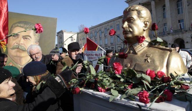 Georgians put flowers on the Soviet dictator Joseph Stalin's monument in his home town of Gori, some 80 km (50 miles) west of the Georgian capital Tbilisi, Georgia, Wednesday, Dec. 21, 2016. (AP Photo/ Shakh Aivazov)
