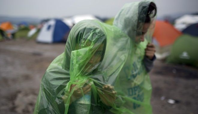 Two girls wearing raincoats walk in front of tents, as refugees wait to be allowed to cross the the Greek-Macedonian border near the northern Greek village of Idomeni , Wednesday, Feb. 24, 2016. The Greek interior ministry said about 12,000 people have been stranded in Greece since neighbor Macedonia began turning Afghan immigrants away at the border and slowing the number of crossings for others heading to central and northern Europe. (AP Photo/Petros Giannakouris)