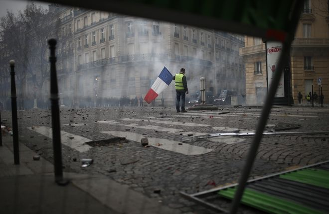 Διαδηλωτής με σημαία της Γαλλίας εν μέσω συγκρούσεων στο Παρίσι