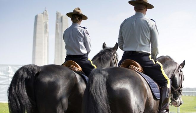 Two Canadian Mounted Police ride their horses toward the WWI Canadian National Vimy Memorial in Givenchy-en-Gohelle, France on Friday, April 7, 2017. Commemoration ceremonies will take place on Sunday at the memorial to honor Canadian soldiers who were killed or wounded during the Battle of Vimy Ridge in April 1917. (AP Photo/Virginia Mayo)