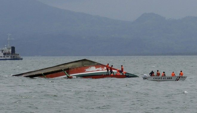 Rescuers stand on a capsized ferry boat in Ormoc city on Leyte Island, Philippines, Thursday, July 2, 2015. A ferry capsized Thursday as it left a central Philippine port in choppy waters, leaving dozens dead and many others missing, coast guard officials said. (Ignatius Martin/Miquicar Photostudio via AP)