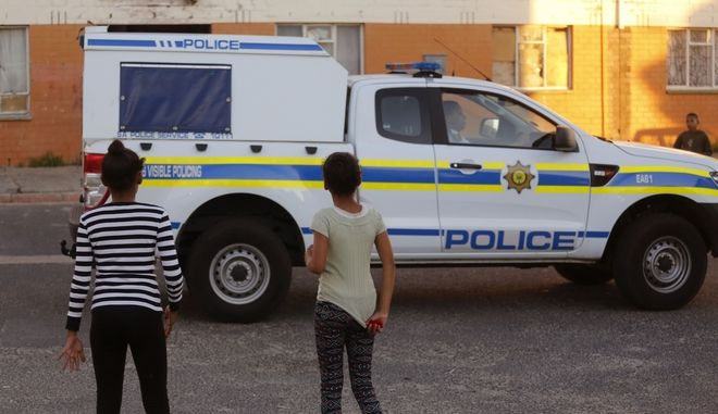 In this photo taken Friday, May 6, 2016, two girls stand as a South African Police truck drives through Atlantis area on the outskirts of  Cape Town, South Africa. Every Friday afternoon, some South African boys head for the sand dunes that surround Atlantis, a poor area on Cape Towns outskirts where drug gangs operate and shootings occur regularly. (AP Photo/Schalk van Zuydam)