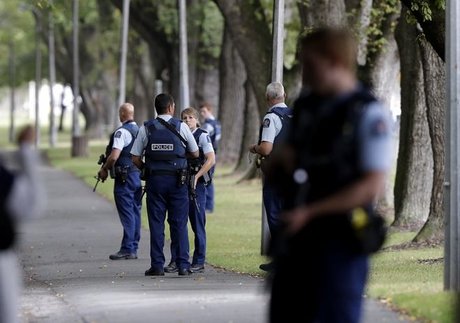 Police keep watch at a park across the road from a a mosque in central Christchurch, New Zealand, Friday, March 15, 2019.  Multiple people were killed in mass shootings at two mosques full of people attending Friday prayers, as New Zealand police warned people to stay indoors as they tried to determine if more than one gunman was involved. (AP Photo/Mark Baker)