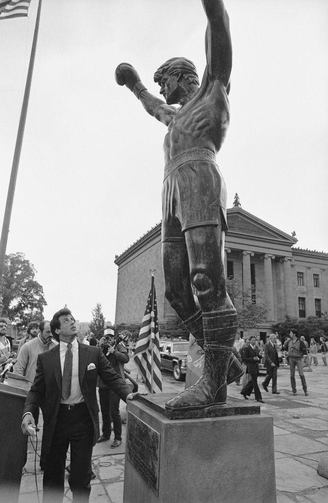 Ο Σιλβέστερ Σταλόνε κοιτά το άγαλμα του Ρόκι που τοποθετήθηκε στα σκαλιά του Μουσείου Τέχνης στη Φιλαδέλφεια. Η φωτογραφία τραβήχτηκε στις 12 Μαΐου 1981, την τρίτη ημέρσ γυρισμάτων του Rocky III.
