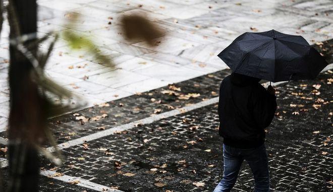 Άνδρας κρατά ομπρέλα κατά τη διάρκεια καταιγίδας