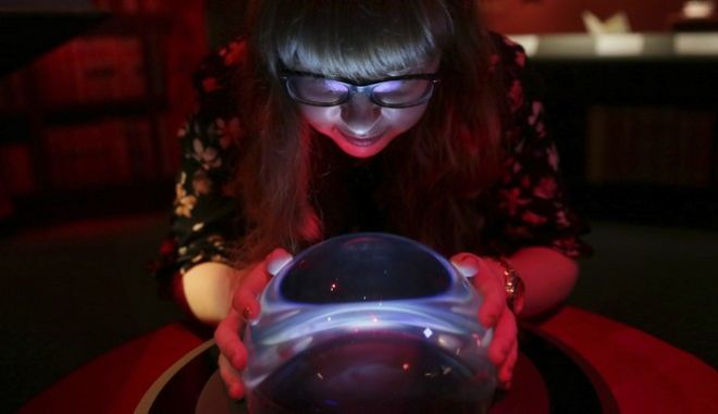 """A member of British Library staff poses with a crystal ball for a picture at the """"Harry Potter - A History of Magic"""" exhibition at the British Library, in London, Wednesday Oct. 18, 2017.  The exhibition running from Oct. 20, marks the 20th anniversary of the publication of Harry Potter and the Philosopher's Stone, showing items from the British Library's collection, and items from author J.K Rowling and the book publisher's collection. (AP Photo/Tim Ireland)"""