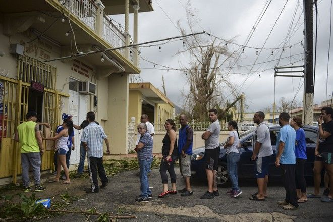 People wait in line to buy bread at Ortiz bakery after the passing of Hurricane Maria, in Yabucoa, Puerto Rico, Thursday, September 21, 2017. As of Thursday evening, Maria was moving off the northern coast of the Dominican Republic with winds of 120 mph (195 kph). The storm was expected to approach the Turks and Caicos Islands and the Bahamas late Thursday and early Friday. (AP Photo/Carlos Giusti)