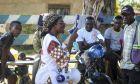Εθελόντρια του Ερυθρού Σταυρού ενημερώνει τους πολίτες του Κονγκό για έμπολα και κορονοϊό.