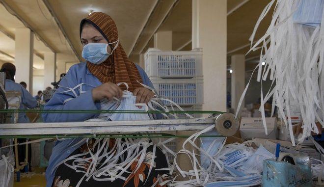 Γυναίκα ράβει μάσκες στην Αίγυπτο (AP Photo/Nariman El-Mofty)