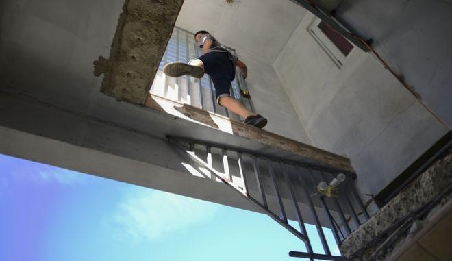 Ένας νέος σκαρφαλώνει στο κατεστραμμένο από το σεισμό σπίτι της θείας του, στο Πουέρτο Ρίκο.