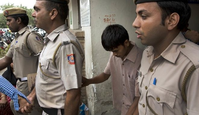 One of the five convicted men in the gang rape of a 51-year-old Danish tourist in 2014, is escorted from court by police in New Delhi, India, Thursday, June 9, 2016. A judge heard arguments by lawyers on the lengths of sentences and said it would be announced on Friday. The five men could face the death penalty or life in prison. (AP Photo/Manish Swarup)