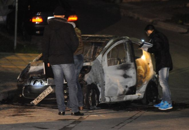 Αστυνομικοί ερευνούν το καμμένο Citroen στην οδό Ηρακλειδών, που χρησιμοποιήσαν οι δράστες στην απόπειρα απαγωγής του γιού του πολύ γνωστού εφοπλιστή Ανδρέα Μαρτίνου, Κίκου Μαρτίνου, έγινε το μεσημέρι στην Βούλα, την Πέμτη 12 Δεκεμβρίου 2013.  Οι δράστες με το κλειστό φορτηγάκι και ένα άσπρο Σιτροέν επιχείρησαν να ακινητοποιήσουν τον γιο του εφοπλιστή την ώρα που ήταν εν κινήσει με το αυτοκίνητό του λίγα μέτρα μακριά από την εφοπλιστική εταιρεία. (EUROKINISSI/ΑΝΤΩΝΗΣ ΝΙΚΟΛΟΠΟΥΛΟΣ)