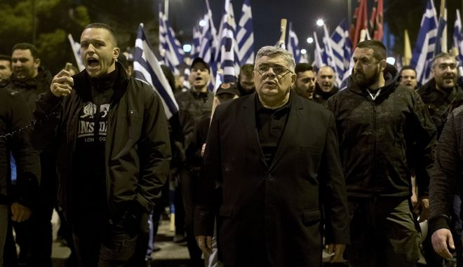 Golden Dawn lawmaker Ilias Kasidiaris , left, shouts slogans next to Golden Dawn party leader Nikos Mihaloliakos during protest in central Athens on Monday, March 5, 2018. About 500 members and supporters of the Nazi-inspired party, which is the fourth-largest in Greece's parliament, took part in the protest which follows the arrest last week, by Turkish forces, of two Greek soldiers patrolling the two countries' land border for allegedly illegally crossing into Turkey. Greek authorities say the soldiers crossed the border by mistake due to bad weather and poor visibility. (AP Photo/Petros Giannakouris)