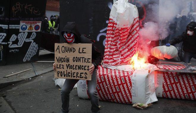 """Διαδηλωτής στη Γαλλία κρατάει πανό που γράφει: """"Εμβόλιο κατά της αστυνομικής βίας"""""""