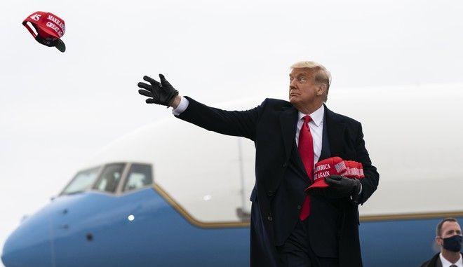 Ο Ντόναλντ Τραμπ πετάει καπέλα σε υποστηρικτές του σε προεκλογική συγκέντρωση