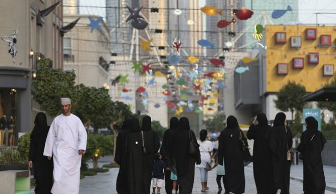 In this Sunday, Aug. 6, 2017, Emirati women spend their free time at the City Walk district in Dubai, United Arab Emirates. The crisis between tiny Qatar and its Arab neighbors is straining the centuries-old cultural and family fabric that binds the energy-rich Gulf states into a common culture, and replacing old taboos with new red lines. (AP Photo/Kamran Jebreili)