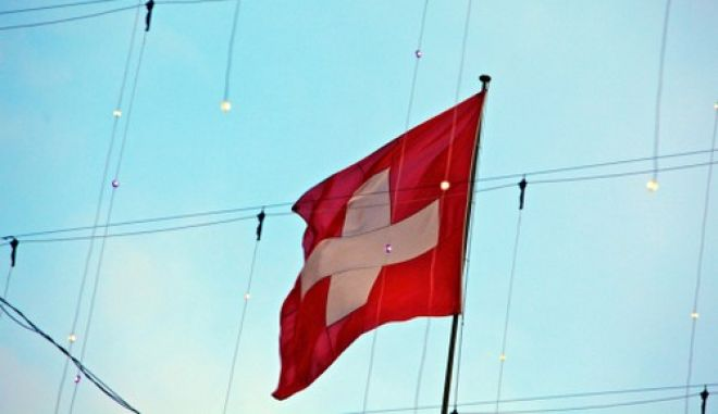 The Swiss national flag flies above buildings in Zurich, Switzerland, on Monday, Dec. 12, 2011. Switzerland?s economy is cooling as the franc?s strength is making exports more expensive just as the euro region edges toward a recession. Photographer:Gianluca Colla/Bloomberg via Getty Images