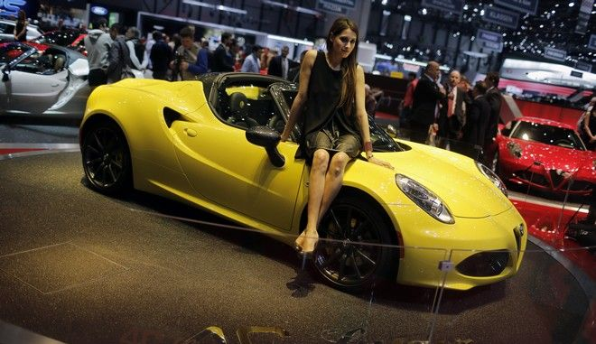 A model sits on the Alfa Romeo 4C Spider during the first press day of the Geneva International Motor Show Tuesday, March 3, 2015 in Geneva, Switzerland. The show opens its doors to the public March 5 through March 15. (AP Photo/Laurent Cipriani)