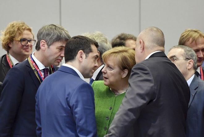 German Chancellor Angela Merkel, center, speaks with Greek Prime Minister Alexis Tsipras, center left, and Bulgarian Prime Minister Boyko Borissov, center right, during a round table at an EU summit at the Europa building in Brussels on Friday, Feb. 23, 2018. European Union leaders meet without Britain Friday looking to plug a major budget hole after Brexit and endorse a plan to streamline the European Parliament by sharing out the country's seats. (AP Photo/Geert Vanden Wijngaert)