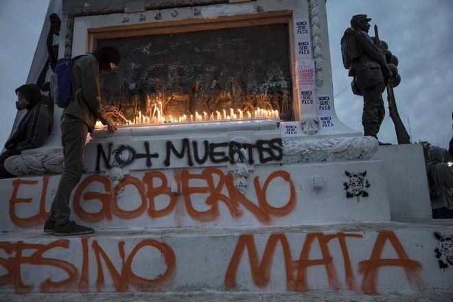 Άντρας ανάβει κερί στη μνήμη των νεκρών διαδηλωτών, Σαντιάγο, Χιλή